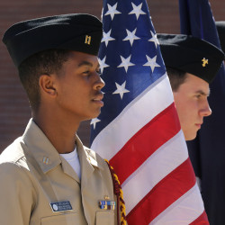 UL Lafayette ROTC students stand with an American flag on Veterans Day.